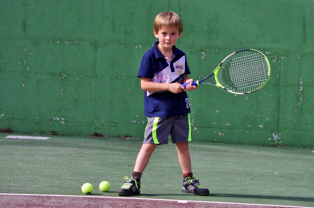 Foto eines Jungen mit Tennisbällen und einem Kindertennisschläger