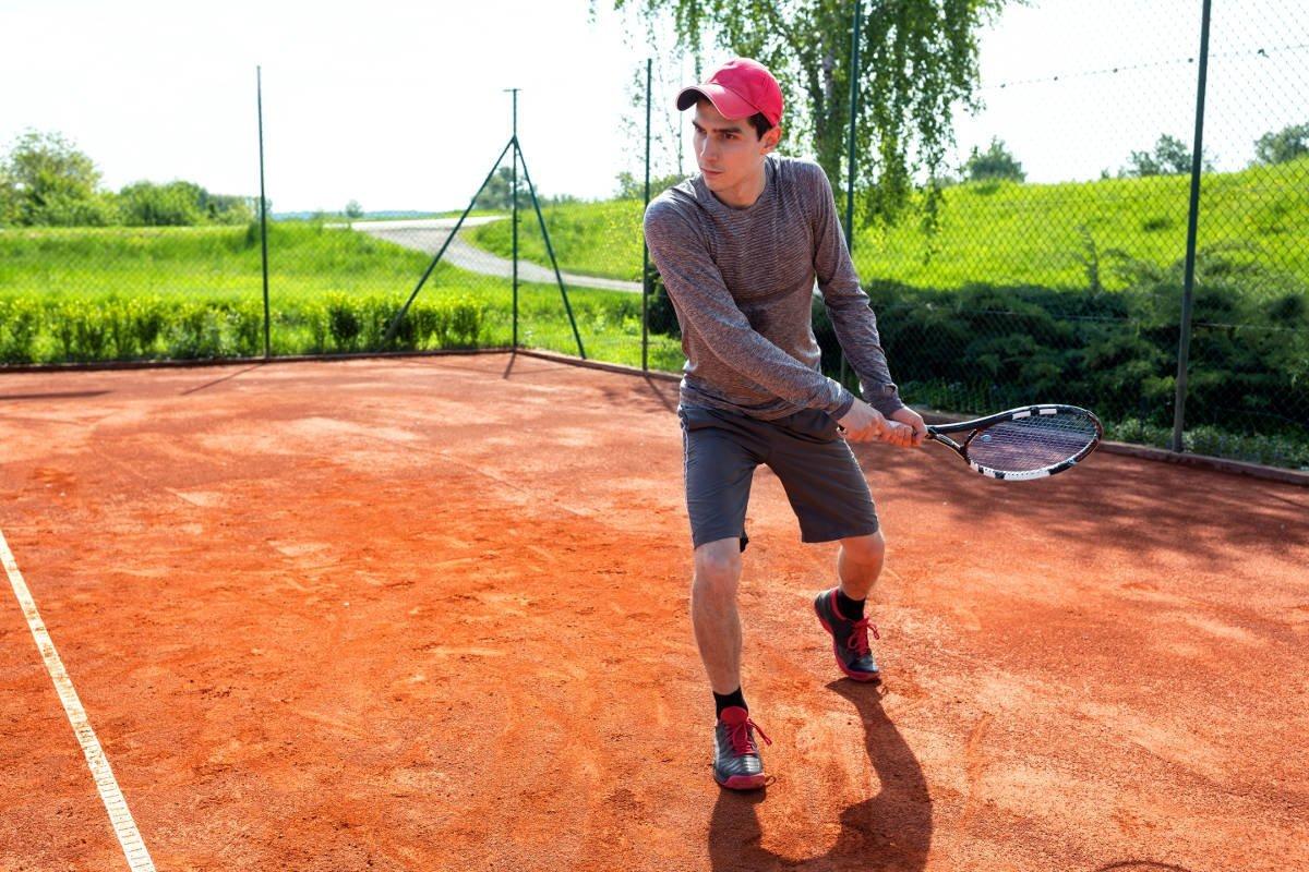 Foto van een tennisser met een shirt met lange mouwen