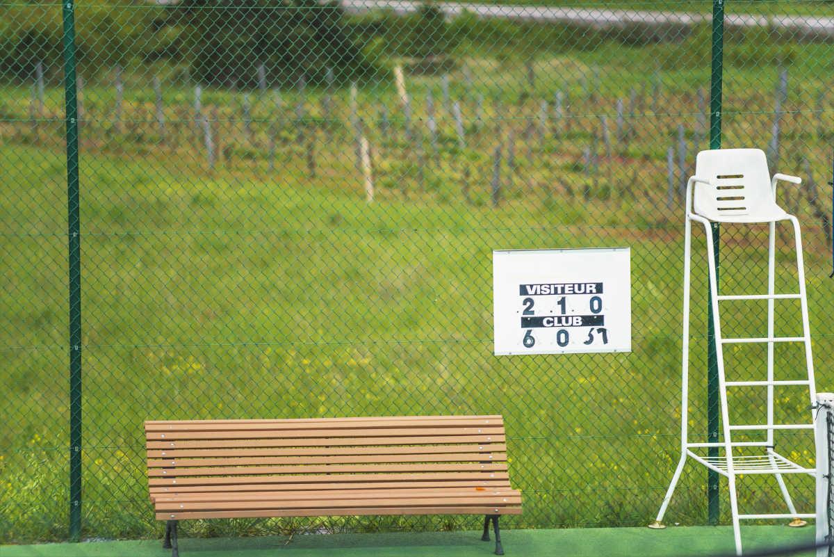 Foto einer Tennis Spielstandsanzeige am Zaum zusammen mit einem Schiedsrichterstuhl