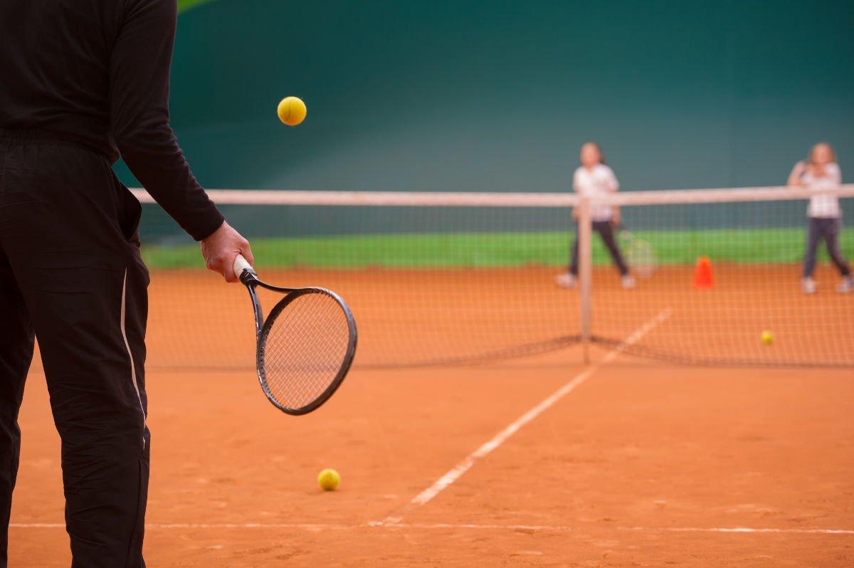 Foto van een tenniscoach met trainingsbroekje
