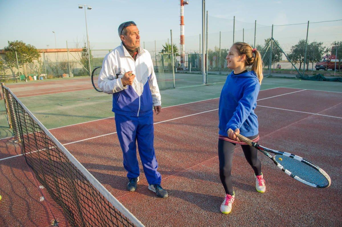 Foto van een tenniscoach en een tennisser met een trainingsjasje