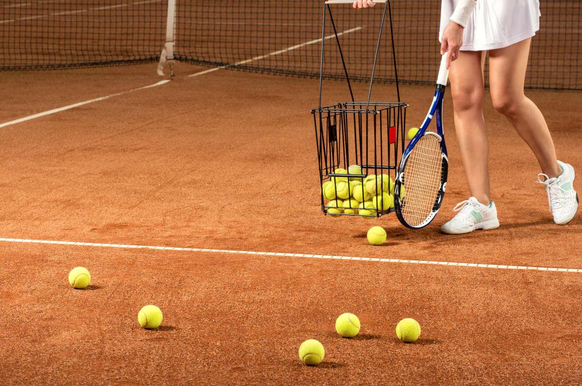 Foto einer Tennisspielerin beim Sammeln von Tennisbällen für die Ballmaschine