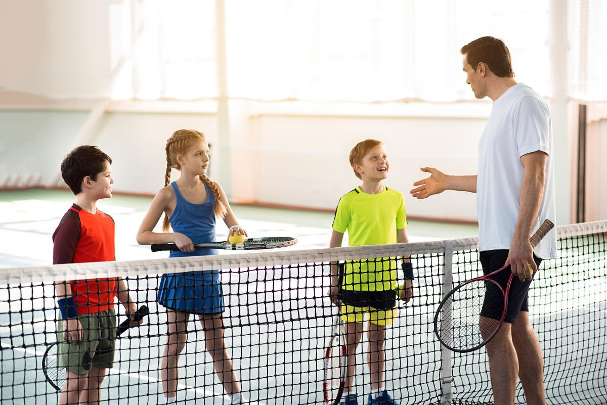 Foto von einem Tennistrainer und von Kindern mit entsprechender Tennisbekleidung