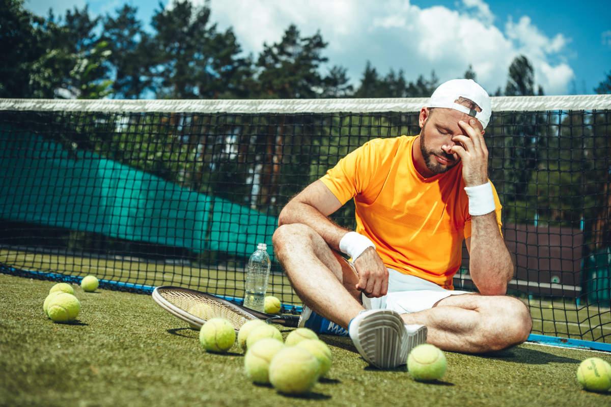 Foto eines enttäuschten Tennisspielers nach einem Fehler