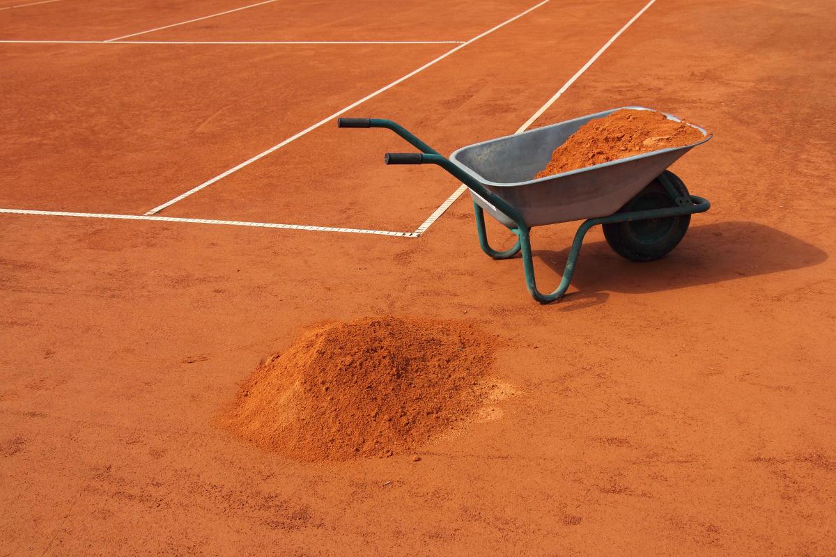 Foto einer Schubkarre mit einem Haufen Ziegelmehl auf dem Tennisplatz