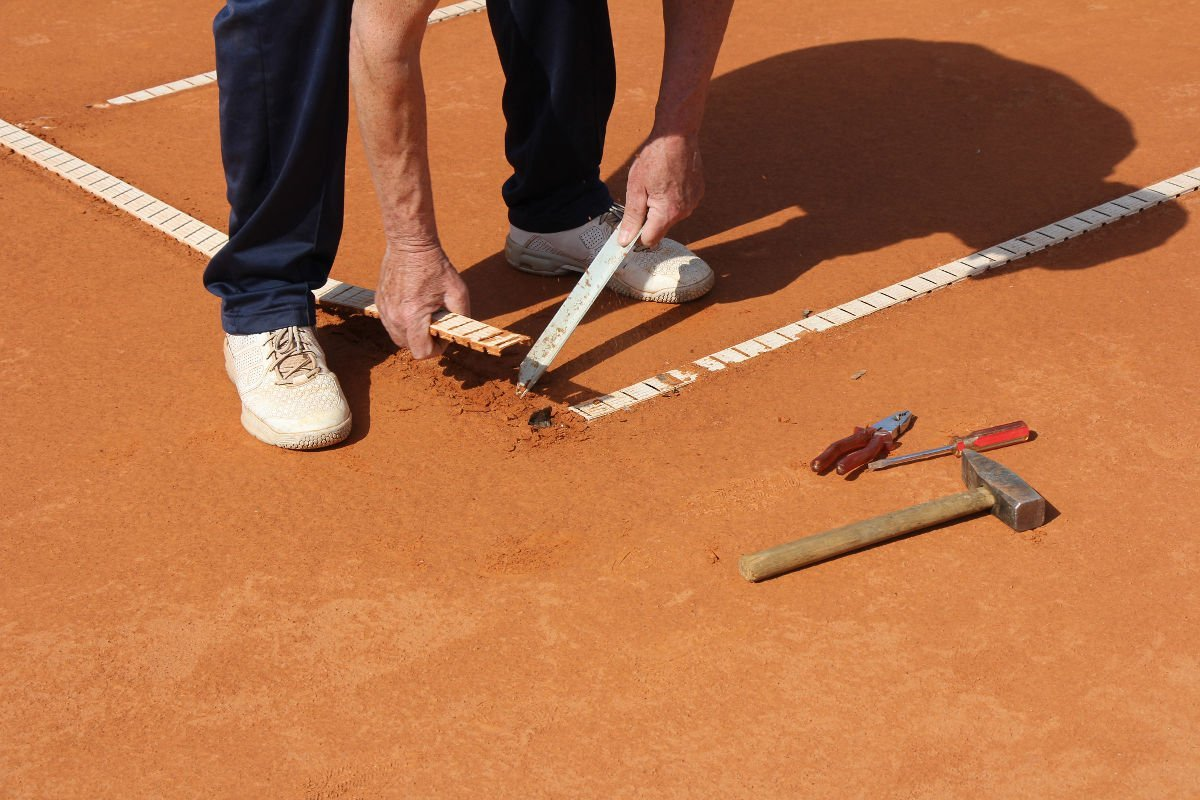 Foto von der Reparatur der Tennislinien auf dem Tennisplatz
