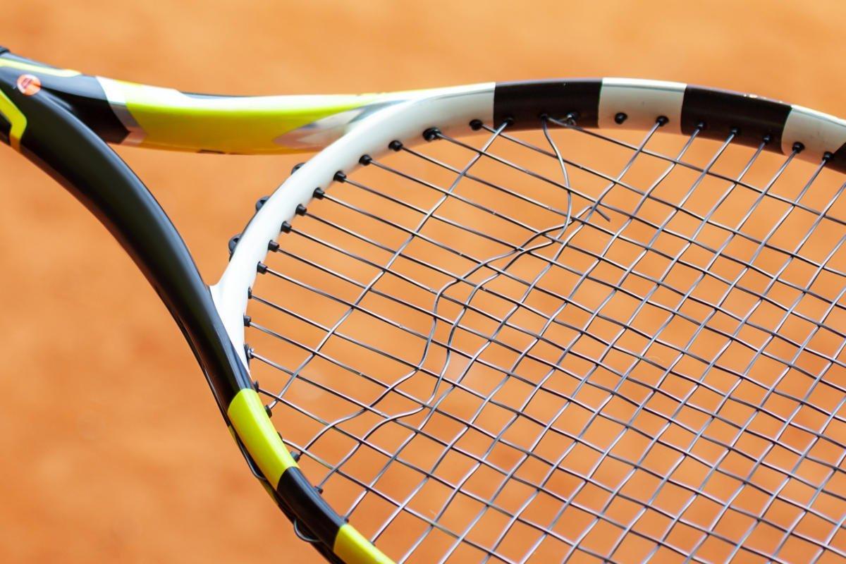 Foto eines Tennisschlägers mit einer gerissenen Tennissaite