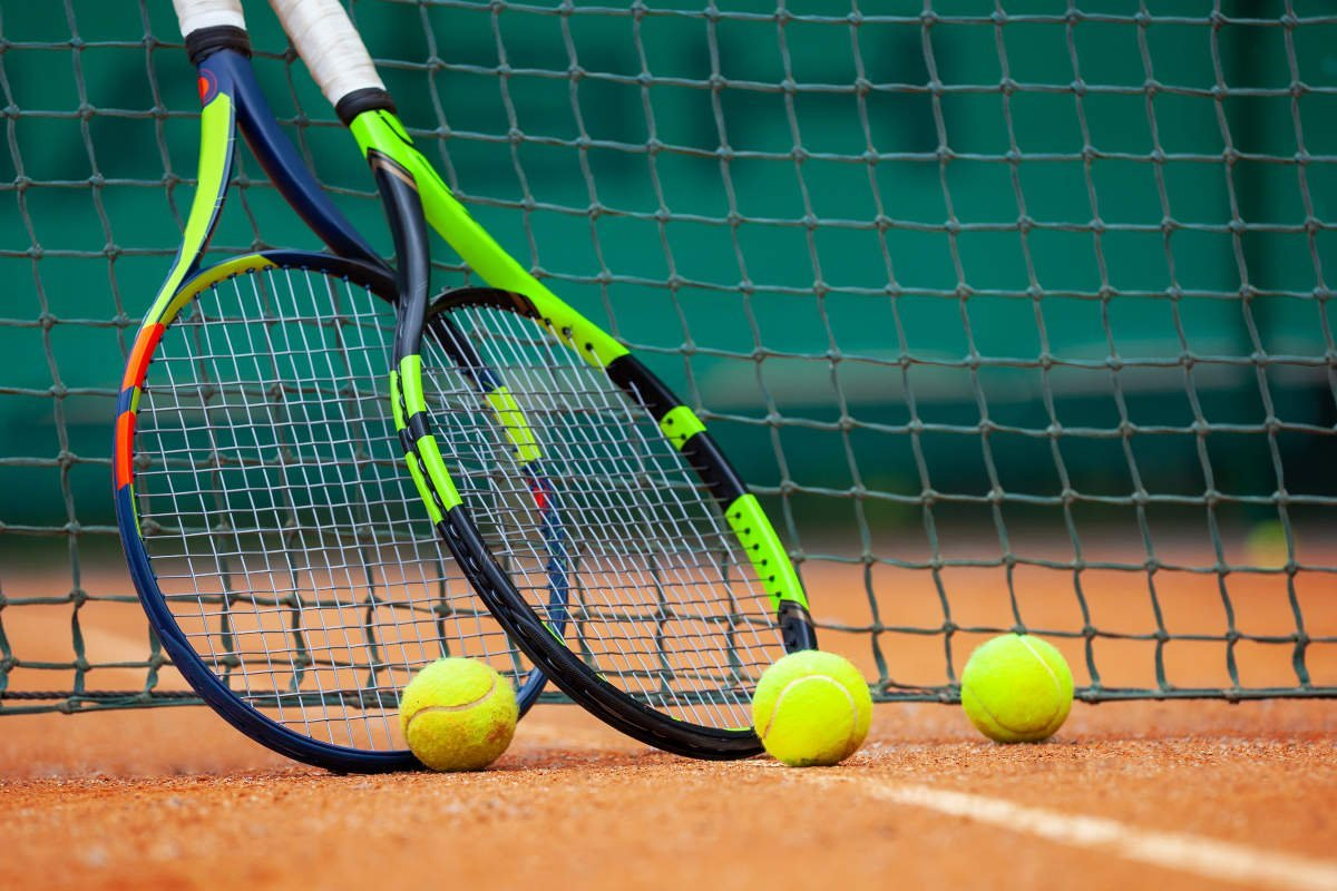 Foto von zwei Tennisschlägern mit Tennisbällen am Netz
