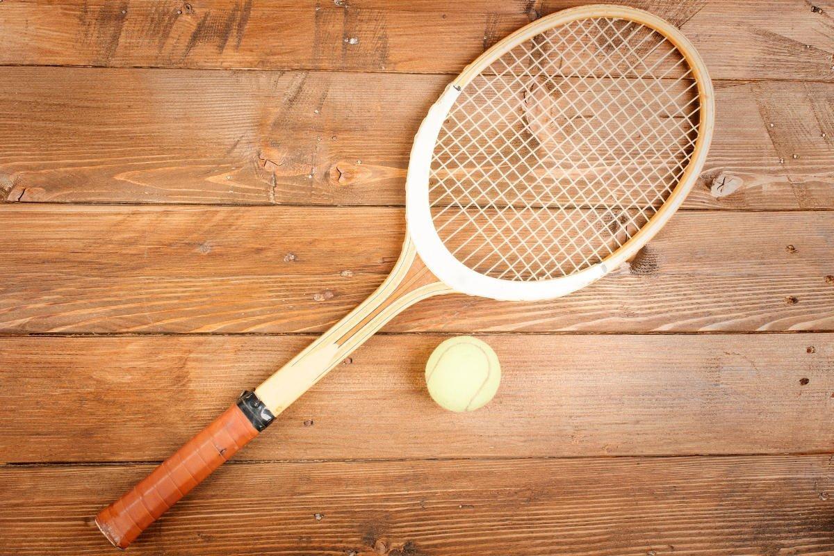 Foto eines Tennisschlägers aus Holz mit einem Tennisball