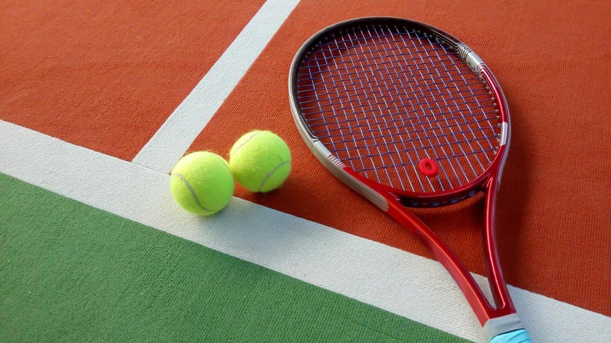 Foto eines Tennisschlägers mit einem Vibrationsdämpfer und zwei Tennisbällen