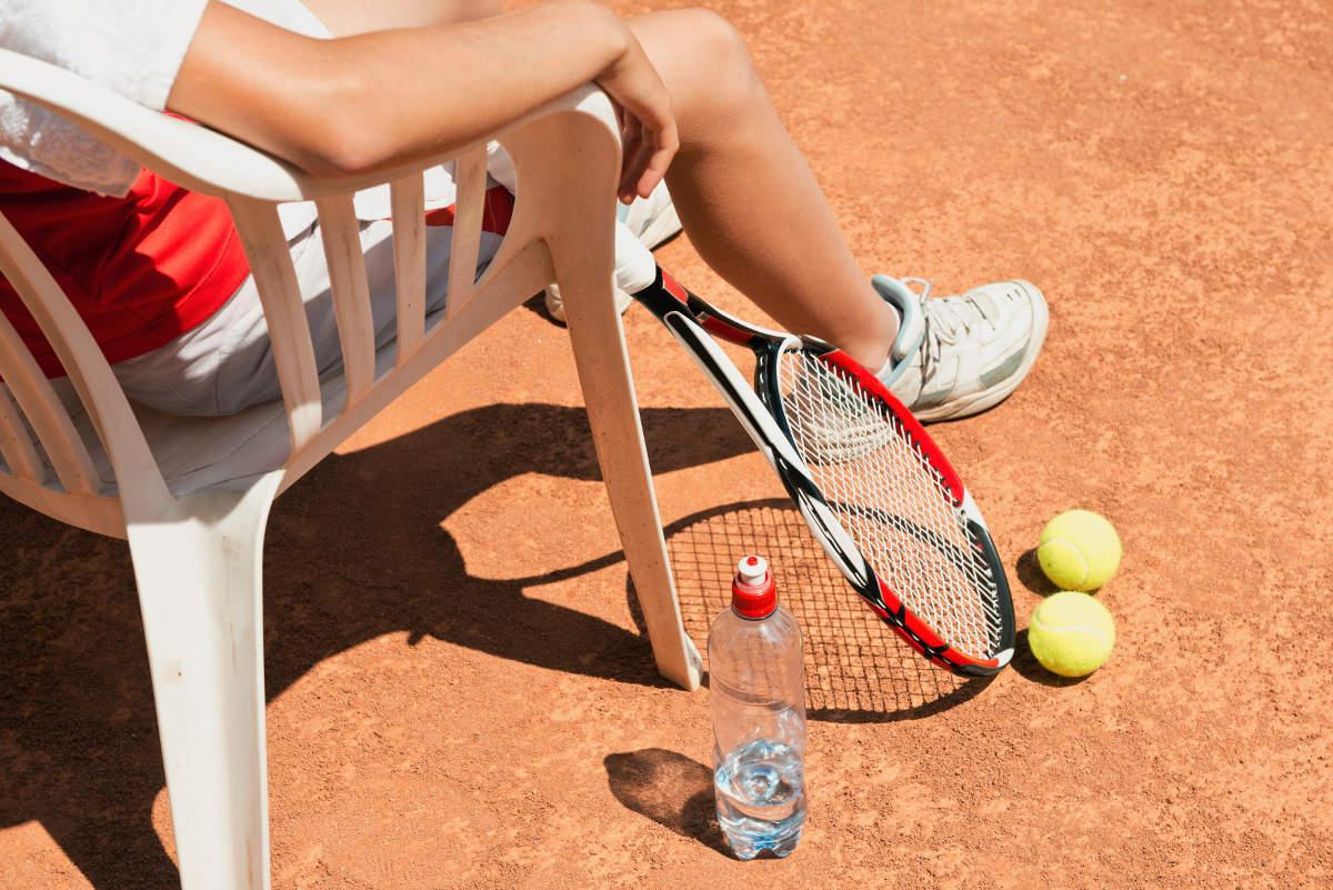 Foto von einer Tennisspielerin mit Tennisschuhen auf einem Stuhl