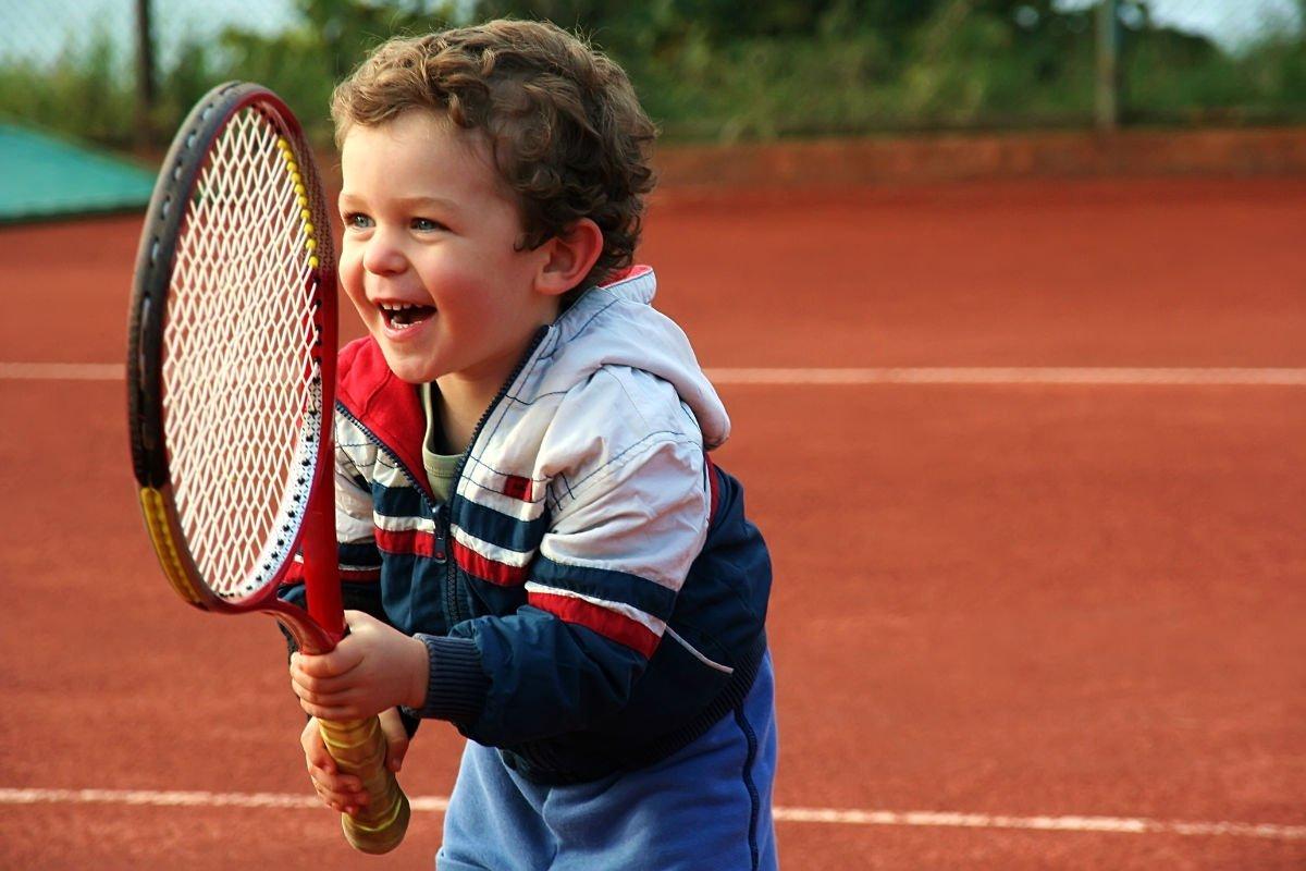 Foto eines Kindes mit einer Trainingsjacke und einem Tennisschläger