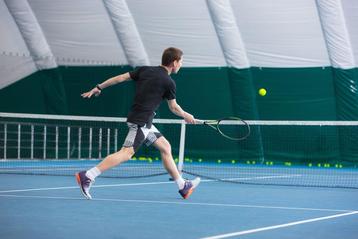 Foto eines Tennisspielers beim Volley in einer Tennishalle