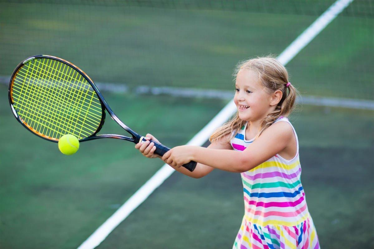 Foto eines Kindes mit einem Tennisschläger und einem Tenniskleid