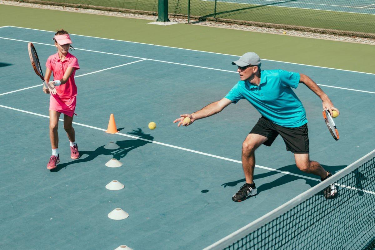 Foto eines Tennistrainers mit einem Kind auf dem Platz