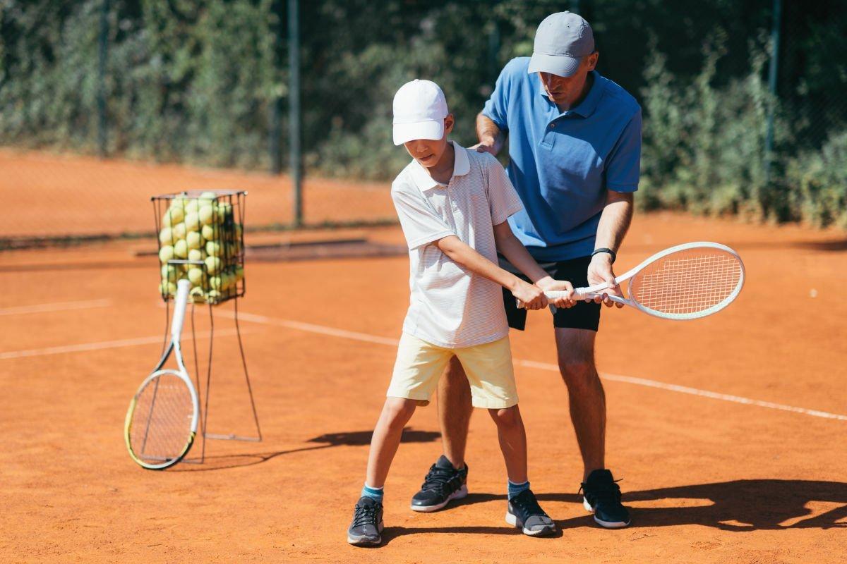 Foto eines Tennistrainers mit einem Schüler auf dem Tennisplatz