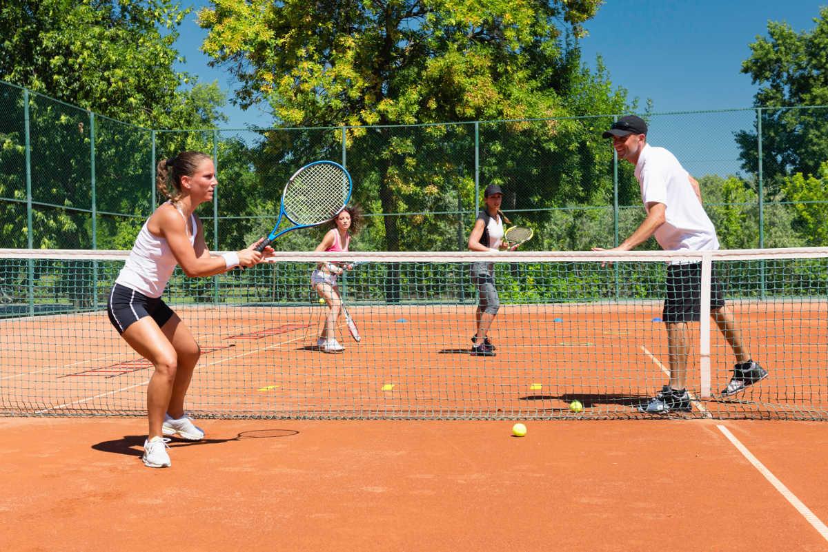 Foto eines Tennistrainers mit mehreren Tennisspielerinnen