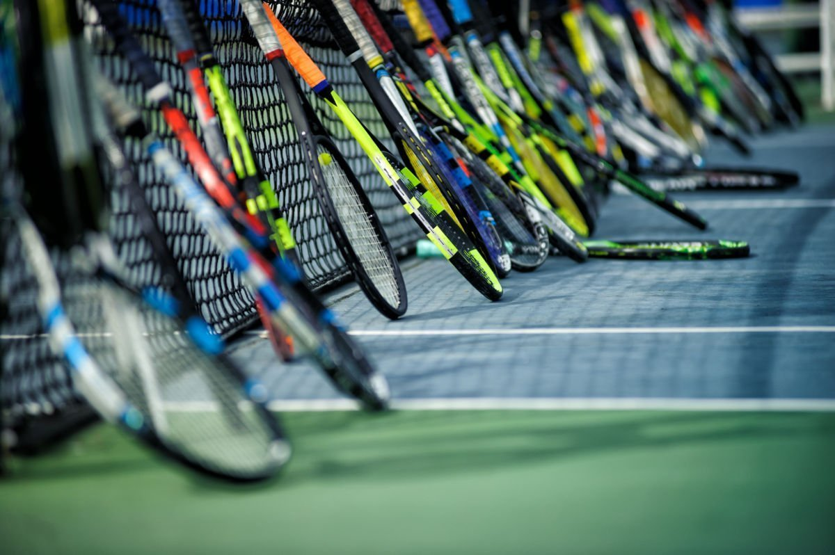 Foto verschiedener Tennisschläger angelehnt an einem Tennisnetz